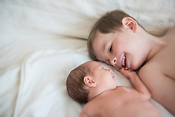 Brother and newborn sister lying on bed, Munich, Bavaria, Germany