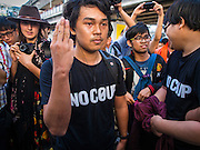 """14 FEBRUARY 2015 - BANGKOK, THAILAND:  An anti-coup protestor holds up the three finger salute from the """"Hunger Games"""" movies during an anti-coup protest in Bangkok. The salute is used by protestors to show opposition to the military government. Showing the salute is grounds for arrest under Thailand's martial law. Dozens of people gathered in front of the Bangkok Art and Culture Centre in Bangkok Saturday to hand out red roses and copies of George Orwell's """"1984."""" Protestors said they didn't support either Red Shirts or Yellow Shirts but wanted a return of democracy in Thailand. The protest was the largest protest since June 2014, against the military government of General Prayuth Chan-Ocha, who staged the coup against the elected government. Police made several arrests Saturday afternoon but the protest was not violent.     PHOTO BY JACK KURTZ"""