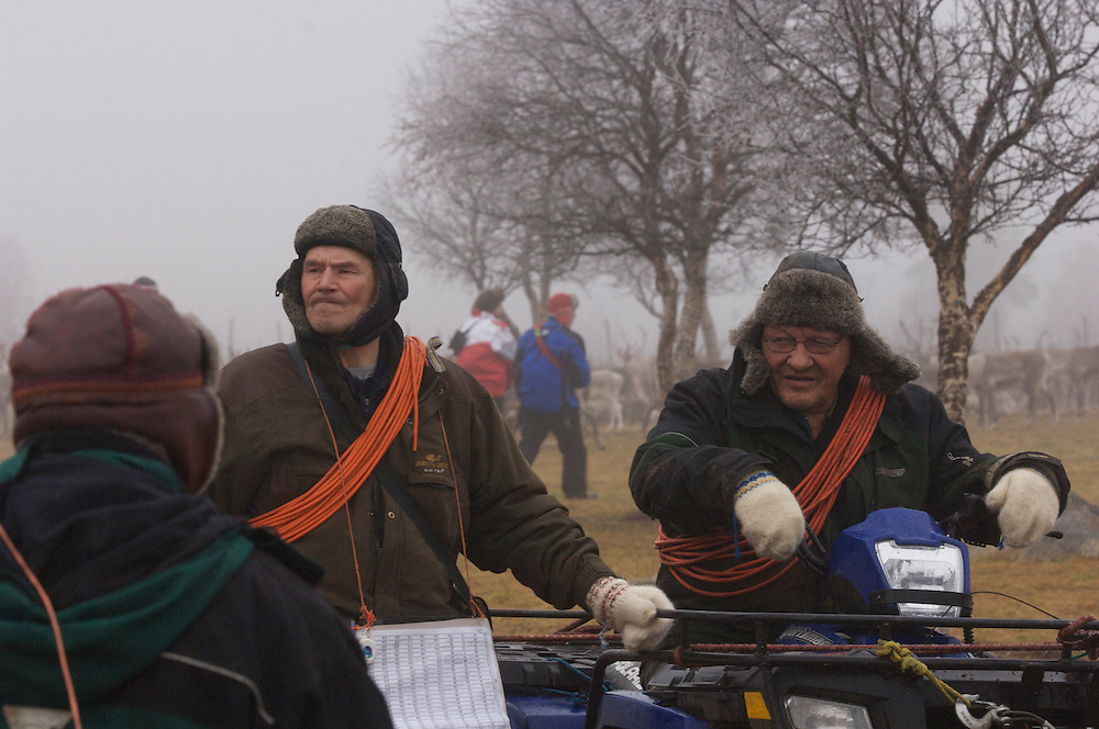 Sami herders seated on their 4x4 wheelers pause during a morning of lassoing.