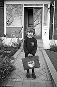 A 5 year-old girl stands outside her south London home on the first day of proper school, a momentous day and a rite of passage. Standing on the path by the front door of an Edwardian period south London home, the girl holds a brand new book bag with the initials of her local school of St Saviour's, repeated on her school jumper. She looks calm but is inwardly nervous of the day about to unfold - a rite of passage for every schoolchild, climbing the ladder of life.