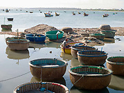 A fisherman fixes his net whilst sitting on a modern plastic coracle amidst a mixture of modern and traditional bamboo coracle fishing boats at the harbour in the coastal fishing village of Chi Cong in Central Vietnam
