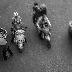Vietnam - Hanoi Streetsellers, Hanoi (from above). <br /> <br /> Like most of her colleagues, this lady is an early riser and cycles from the outskirt into Downtown Hanoi to sell her fruits.I spent hours and hours on bridges, it took me some days to find the right spot. Depending on the colorful arrangement some streetseller are more promising than others. Some are brining in their mobile kitchen to prepare food on the spot. Others offer loads of clothing or even haircuts. There is the coffee guy, flower an veggie ladies, the shoe-shine boy, a karaoke singer duo. One morning I witnessed an old lady pulling a huge mobile scale for instant weighing.