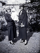 two women posing with baby in garden 1930s