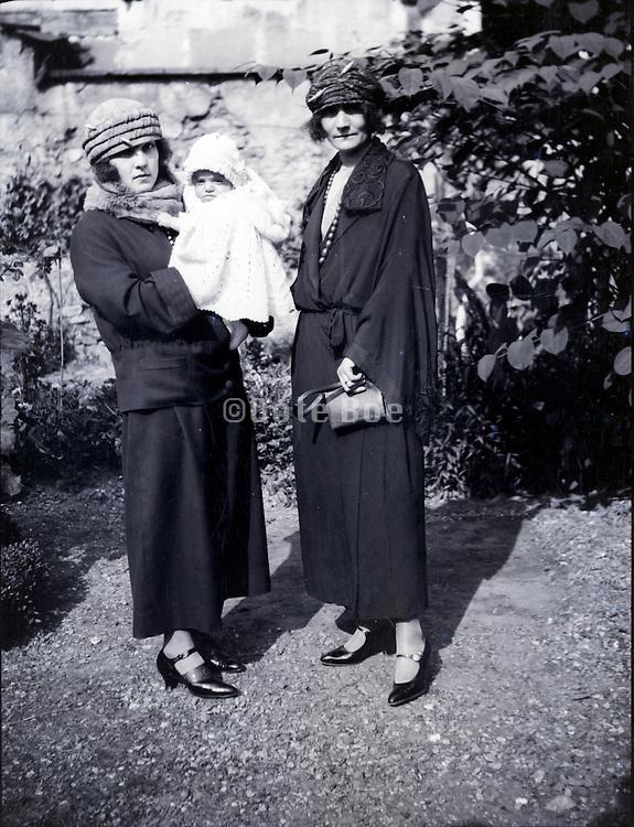 two women posing with baby in garden 1930s