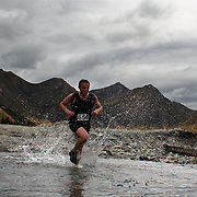 Runner Brendon Martyn crosses Moke Creek on the Ben Lomond High Country Station during the Pure South Shotover Moonlight Mountain Marathon and trail runs. Moke Lake, Queenstown, New Zealand. 4th February 2012. Photo Tim Clayton