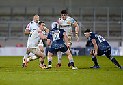 Exeter Chiefs No.8 Sam Simmonds runs at Sale Sharks hooker Curtis Langdon and Sale Sharks flanker Jono Ross during a Gallagher Premiership Round 11 Rugby Union match, Friday, Feb 26, 2021, in Eccles, United Kingdom. (Steve Flynn/Image of Sport)
