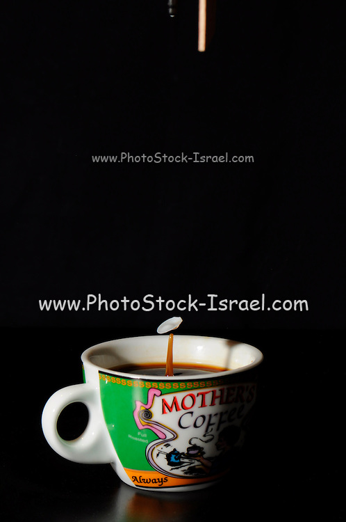 High-speed flash photograph milk drop into a coffee cup. The droplet lands in the liquid and produces a coronet.