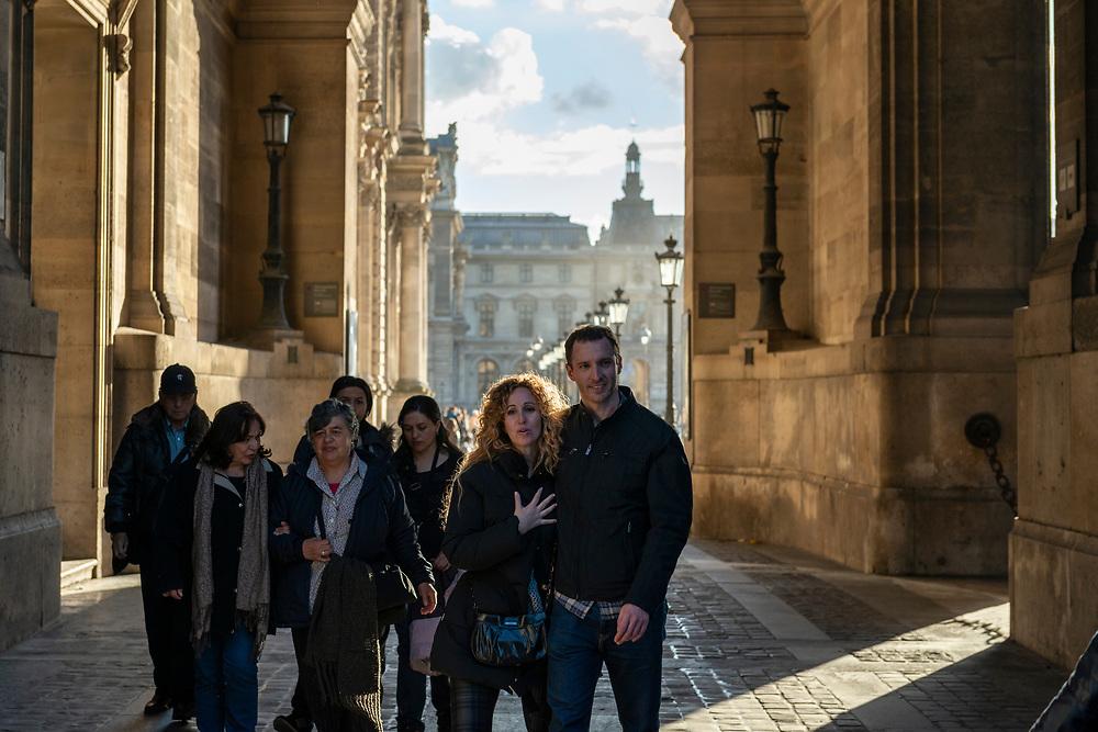 Paris, France - October 30, 2013: Pedestrians walk outside the Louvre, exiting the Place du Carrousel toward Rue de Rivoli.