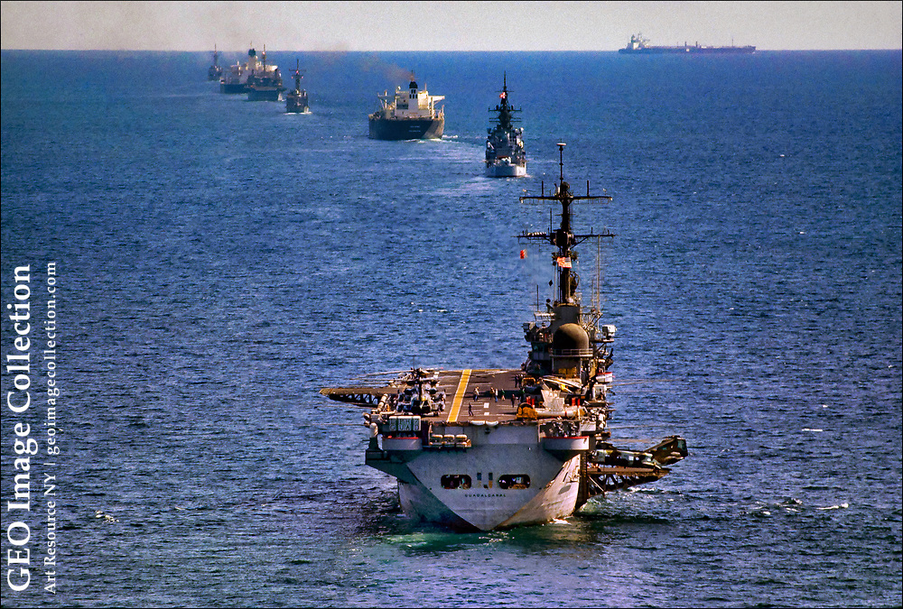 """The amphibious assault ship U.S.S. Guadalcanal, with a flotilla of other American warships, escorts Kuwaiti-owned oil tankers through the Persian/Arab Gulf to protect them from Iranian attacks during the 1987-1988 """"tanker war.""""  """"Operation Earnest Will""""  was the largest naval convoy operation since World War II and frequently involved stand-offs—and shots fired—at Irian Navy and Revolutionary Guards patrol boats."""