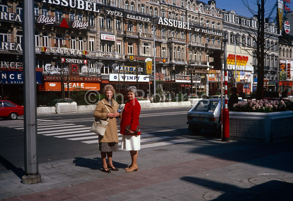 A portrait of two lady friends in Brussels in the 1970s. The two women are on a shopping and sightseeing trip into the Belgian capital in 1978, Clutching bags and some shopping, they stand in the Brussels square called Place de Brouckere in the centre of the city. The signs of cafes and shops are in the background..