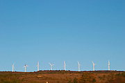 Wind power turbines on a mountain hill top crest against a blue sky. Limoux. Languedoc. France. Europe.
