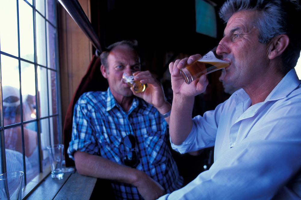 Australia, Tasmania, (MR) Max Long & Darryl Pritchard down beers at Clarendon Arms Hotel pub in downtown Evandale.