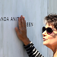 """A visitor to the Flight 93 National Memorial caresses on of the 40 names on the """"Wall of Names"""" near Shanksville, Pa.,  on the 14th observance of the Flight 93 crash and Sept. 11 terrorist attacks. Photo by Archie Carpenter/UPI ."""