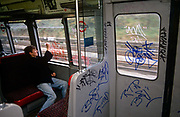 A London youth is busy tagging on windows of a 90s London underground tube train, during an overland section of the capital's rail system near Ladbroke Grove. Armed with heavy-duty semi-permanent marker pens, the lad is committing the crime of defacement and criminal damage to London Underground property, a persistent problem that costs the transport company network up to £3 million a year to remove. Partitions and glass are being scribbled on with their unique identity signatures used by kids of this age to leave as a mark of their presence, like animals instinctively leave a scent on a street corner. If caught, juvenile delinquents like these may escape with only a caution because of their age but older ones are prosecuted, though some times after leaving many thousands of tags across their neighbourhood.