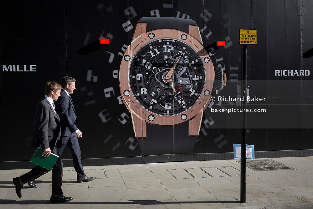 Two businessmen walks past a construction hoarding of a watch outside the new Richard Mille shop in New Bond Street, on 25th February 2019, in London, England.
