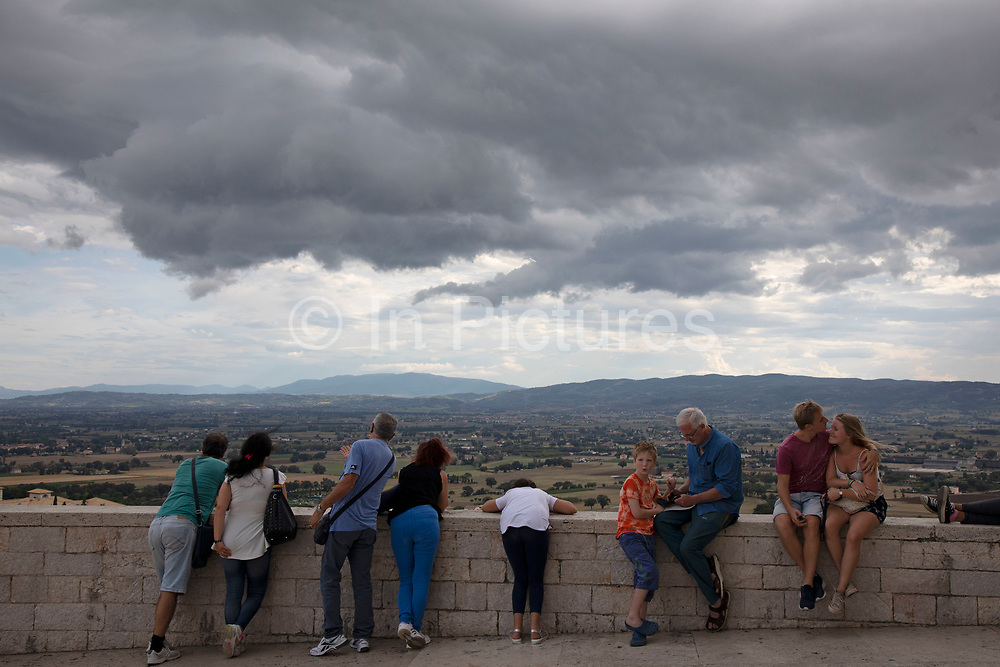 Tourists outside the Basilica of San Francesco dAssisi in Assisi, Umbria, Italy. The Papal Basilica of Saint Francis of Assisi is the mother church of the Roman Catholic Order of Friars Minor Conventual in Assisi, a town of Umbria region in central Italy, where Saint Francis was born and died. The basilica is one of the most important places of Christian pilgrimage in Italy. Assisi is a town in the Province of Perugia in the Umbria region, on the western flank of Monte Subasio. It is generally regarded as the birthplace of the Latin poet Propertius, and is the birthplace of St. Francis, who founded the Franciscan religious order in the town in 1208, and St. Clare, Chiara dOffreducci, the founder of the Poor Sisters, which later became the Order of Poor Clares after her death. Assisi is now a major tourist destination for those sightseeing or for more religious reasons.