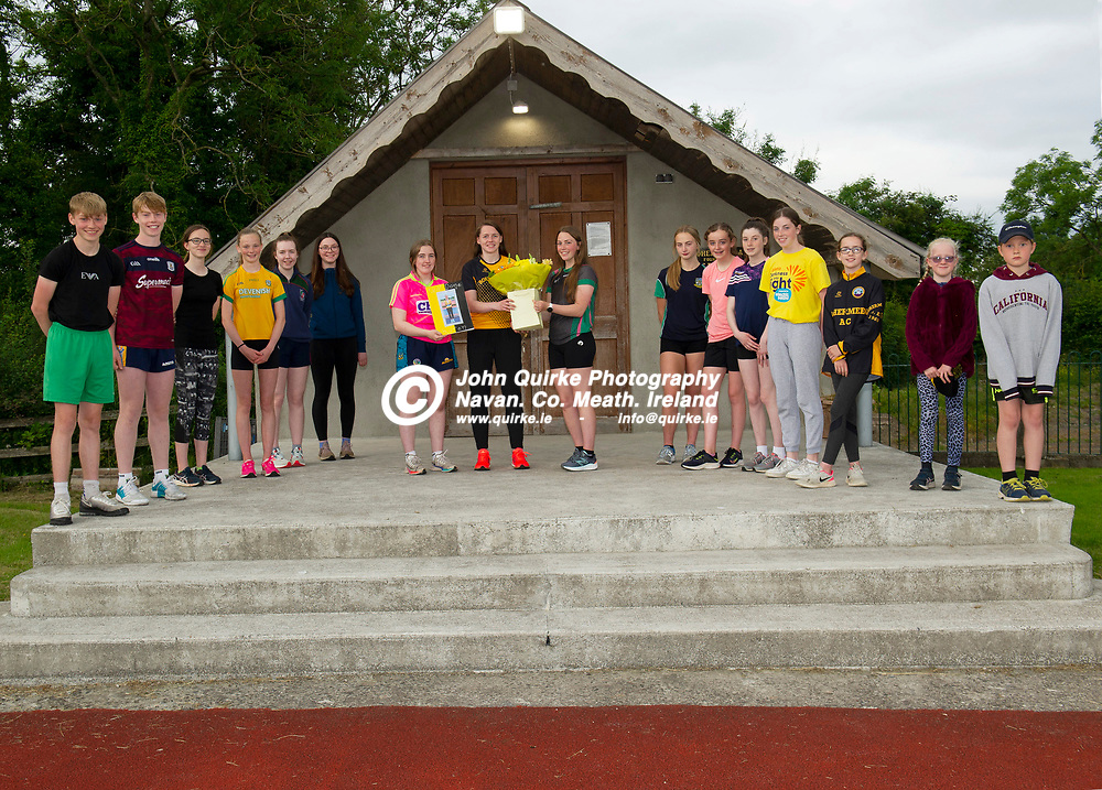 02-07-21. Bohermeen Athletic Club Presentation to Kevin McGrath and Karen Dunne.<br />Emma Kate Ball (Left) and Aisling Davis making a presentation to Karen Dunne,  Nation Track and Field 800 Hurdles bronze medalist with from left, Killian Yore, Tiernan Anderson, Dannu McGann, Aideen Davis, Mollie Kandley, Beth Miskelly, Rebecca Reilly, Amy Keoghan, Cara Brennan, Eva Brennan, Inga McGann, Lilly Reilly and Kevin Reilly.<br />Photo: John Quirke / www.quirke.ie<br />©John Quirke Photography, 16 Proudstown Road, Navan. Co. Meath. (info@quirke.ie / 046-9028461 / 087-2579454).