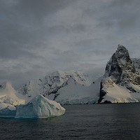 Mountains on the Antarctic Peninsula tower above the Lemaire Channel, a popular cruise ship destination in Antarctica.
