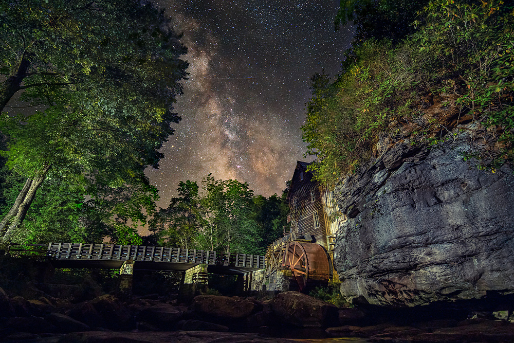 The core of the MIlky Way can be seen just above the tree line and the grist mill on a late summer night in Babcock State Park, West Virginia.