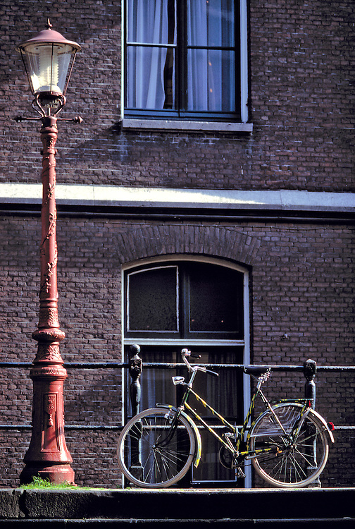 A bicycle waits for its rider, near a striking red lampost, in Amsterdam, Netherlands.