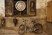Bicycle leans against a wall beneath a shuttered window. Italy.
