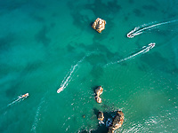 Aerial view of four boats navigating around rock pillars in the sea in portugal.