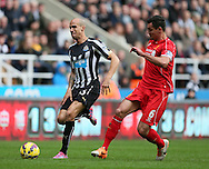 Gabriel Obertan of Newcastle United pulls up injured as he runs to gain possession with Dejan Lovren of Liverpool - Barclays Premier League - Newcastle Utd vs Liverpool - St James' Park Stadium - Newcastle Upon Tyne - England - 1st November 2014  - Picture Simon Bellis/Sportimage