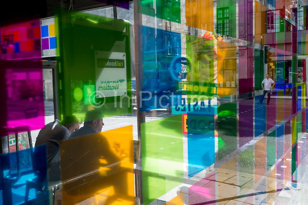 Figures seen through coloured-squared light in a corner cafe on Fleet Street in the City of London, the capitals financial district aka the Square Mile, on 22nd August 2019, in London, England.