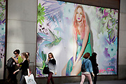 People outside Miss Selfridge retail store dwarfed in scale in front of the large photographic advertising hoardings dipicting slender models. Shoppers in central London on Oxford Street. UK.