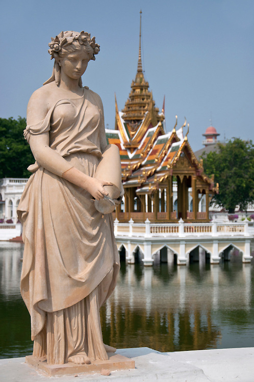 East meets West. Western style statue against the backdrop of traditional Thai architecture.