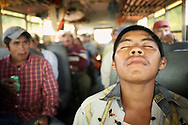 Migrant worker Jose Armando, 18, of Nayarit, Mexico takes  a moment to rest as he rides the camp bus from one peach field to another. His first year as a migrant worker at Titan Farms, Armando took a while to get acclimated to the long work days in the blistering South Carolina sun.