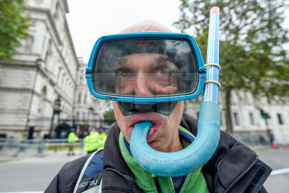 © Licensed to London News Pictures. 08/10/2019. LONDON, UK.  A climate activist outside Downing Street wears a scuba mask and snorkel to demonstrate against rising sea levels on day two of Extinction Rebellion's protest which is planned to close-down Westminster and other areas in the capital for two weeks.  Demonstrators are calling on the Government's immediate action to tackle the negative effects of climate change.  Photo credit: Stephen Chung/LNP
