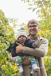 Portrait of a father holding his baby son in his arms and smiling, Bavaria, Germany
