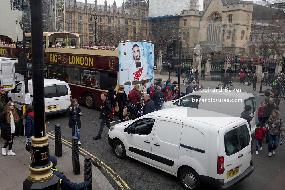 Pedestrians cross the road in front of stationary traffic in Parliament Square, on 8th April 2019, in London, England