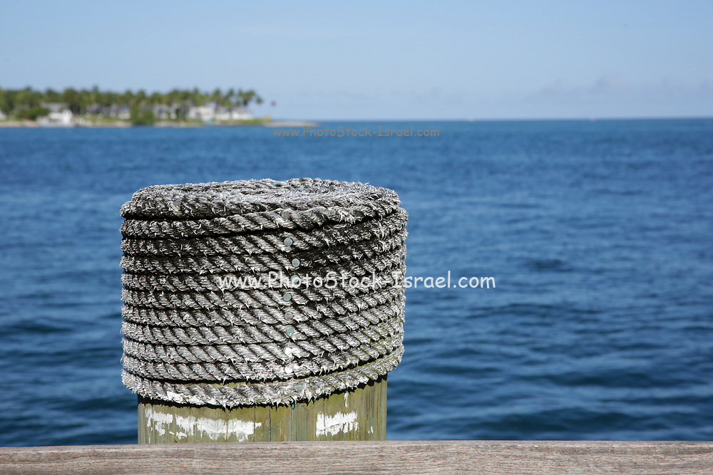 Weathered rope coated bollard for securing boats on a wharf at Key West, Florida, USA