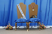 The chairs for the next Torbay Carnival Princess and Queen competition winners awaits their newest occupants during the seaside town's fair in Devon, England. A crown, hat and two bouquets of flowers are for the young girls too and the sash has the words 'Princess for a Day' across the material. The theme of the stage is blue, with matching colours on both cushions and the backing curtain (drapes). There is no one in this landscape but we get a sense of the tacky and old-fashioned nature of the carnival and of its princess competition.