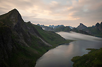 Fog forms amongs the mountains surrounding Forsfjord, Moskenesøy, Lofoten Islands, Norway