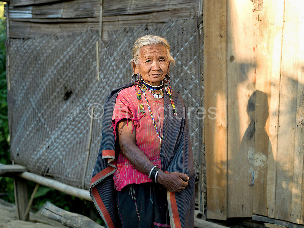 Portrait of  Kayaw ethnic minority woman wearing traditional clothing on 19th January 2016 in Kayah State, Myanmar. Wearing traditional costumes made from handwoven cotton, Kayaw women wear many necklaces made from shells, beads and brass coils and fashioned from silver. Distended earlobes are plugged with rings of silver and the ankles and knees encased with brass coils