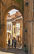 A street in the old medieval village of Saint Emilion, Bordeaux. three people a family walking on the street.