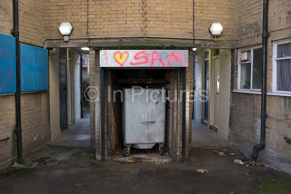 Someone has sprayed grafitti reading 'I love Sam' in an area by the refuse bins on a council estate in North London, UK. A declaration of love in unlikely surroundings.