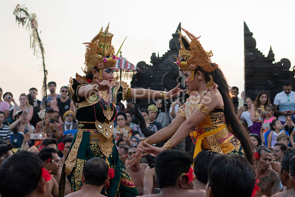 Female dancers wearing traditional costumes participate in the Kecak fire dance, which takes place at the Pura Luhur Uluwatu Temple at the southernmost tip of the island on 17th June, 2018 in Bali, Indonesia. It is a sacredly positioned temple, believed to protect the island from evil spirits, and the fire dance performance is an adaptation of the Ramayana Hindu story.