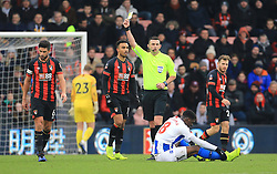 Bournemouth's Andrew Surman (left) is shown a yellow card by referee Michael Oliver (centre) during the Emirates FA Cup, third round match at the Vitality Stadium, Bournemouth.