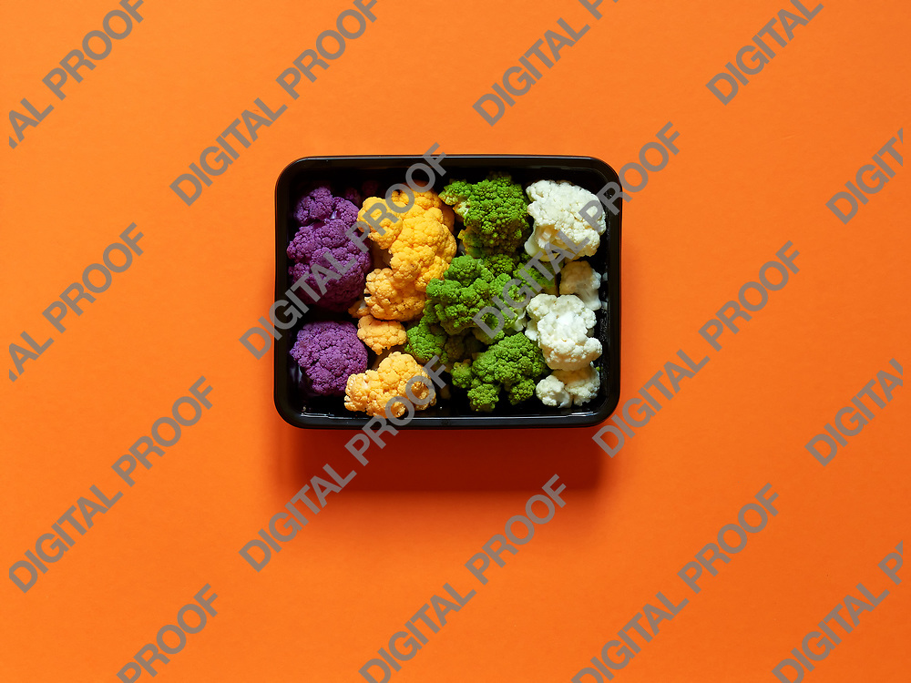 Set of seasonal and colorful cauliflower violet, yellow, green and white boxed in a plastic recipient over an orange background