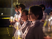 """11 FEBRUARY 2016 - KHLONG LUANG, PATHUM THANI, THAILAND:  People participate in the procession around the pagoda during the Makha Bucha Day service at Wat Phra Dhammakaya.  Makha Bucha Day is a public holiday in Cambodia, Laos, Myanmar and Thailand. Many people go to the temple to perform merit-making activities on Makha Bucha Day, which marks four important events in Buddhism: 1,250 disciples came to see the Buddha without being summoned, all of them were Arhantas, or Enlightened Ones, and all were ordained by the Buddha himself. The Buddha gave those Arhantas the principles of Buddhism. In Thailand, this teaching has been dubbed the """"Heart of Buddhism."""" Wat Phra Dhammakaya is the center of the Dhammakaya Movement, a Buddhist sect founded in the 1970s and led by Phra Dhammachayo. Makha Bucha Day is one of the most important holy days on the Thai Buddhist calender.     PHOTO BY JACK KURTZ"""