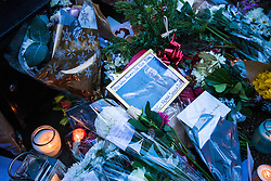 Highgate, London, December 26th 2016. Fans gather outside the London home of pop icon George Michael who died on Christmas day. PICTURED: Candles, flowers and a framed picture of George Michael are among the many tributes.