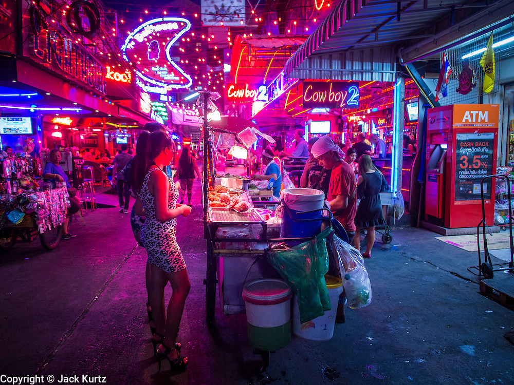 """22 MAY 2014 - BANGKOK, THAILAND:  A food vendor does business on Soi Cowboy, one of Bangkok's """"adult entertainment"""" districts, after the army announced a coup and overnight curfew. The Thai army suspended civilian rule, suspended the constitution and declared the """"military takeover of the nation."""" The announcement came just before evening as a meeting between civilian politicians and the army was breaking up with no progress towards resolving the country's political impasse. Civilian politicians were arrested when the meeting ended. The army also declared a curfew from 10PM until 5AM.   PHOTO BY JACK KURTZ"""