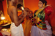 An actor checks his make up in a mirror held by a senior student before a performance of the Ramayana at the Kerala Kalamandalam.The Kalamandalam was founded in the 1930's to preserve the ancient forms of Keralan arts and dance of which Kathikali, a mute mixture of ballet and drama is the most well known..Cherathuruty, Kerala, India