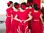 A group of Laotian girls wearing red dresses before their dance performance at the Women's International Group (WIG) bazaar, Vientiane, Lao PDR. The WIG Bazaar is a charity event aiming to raise funds for projects benefitting Lao women and children.