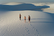 Three people walking in waves in the sand, White Sands National Monument, New Mexico, USA
