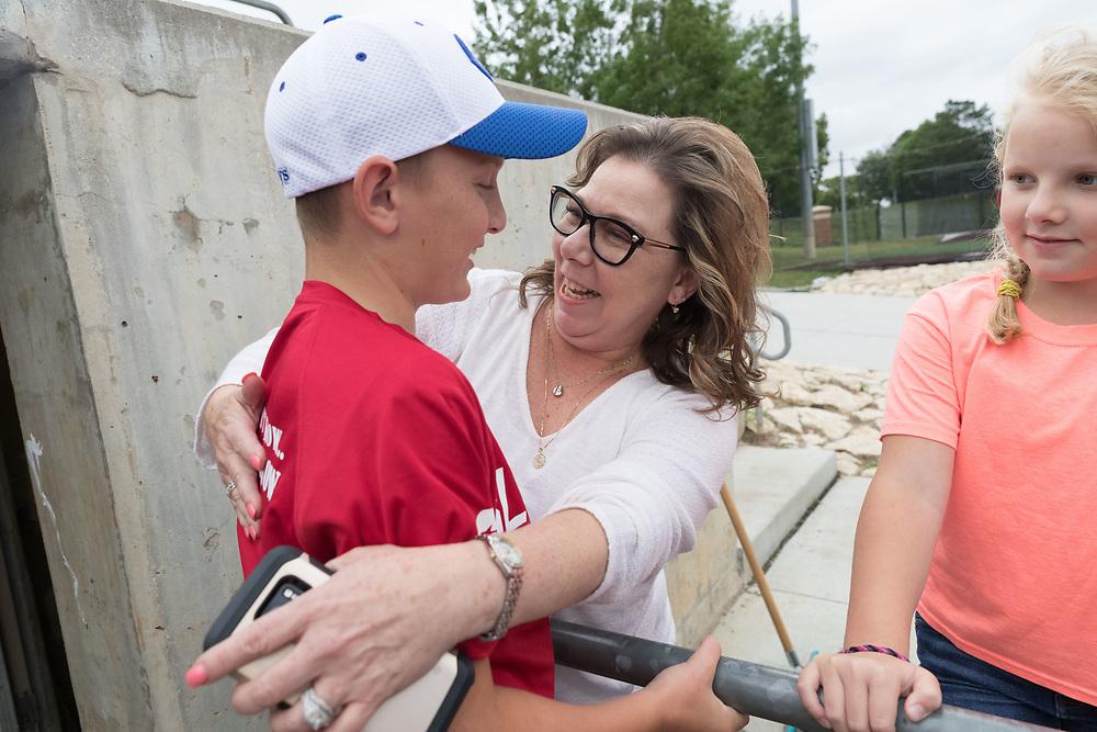 Grayson Gilbert, 11, gets a hug from Donna Wellwood-Clawson, mother of coach Jerry Wellwood. Post 1 Omaha, Nebraska, played Post 307 Renner, South Dakota, in a legion baseball game at Creighton Prep on Wednesday, June 20, 2018, in Omaha, Nebraska.